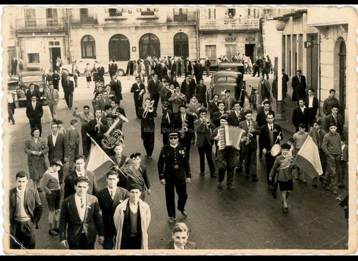 Rondalla de Mosende desfilando pola praza da Central do Porriño. / Foto Ramiro [Ca. 1960] / PROCEDENCIA: Recollida de Mosende. Albumes familiares de Juan Gallego e Jaime Bugarín Alonso