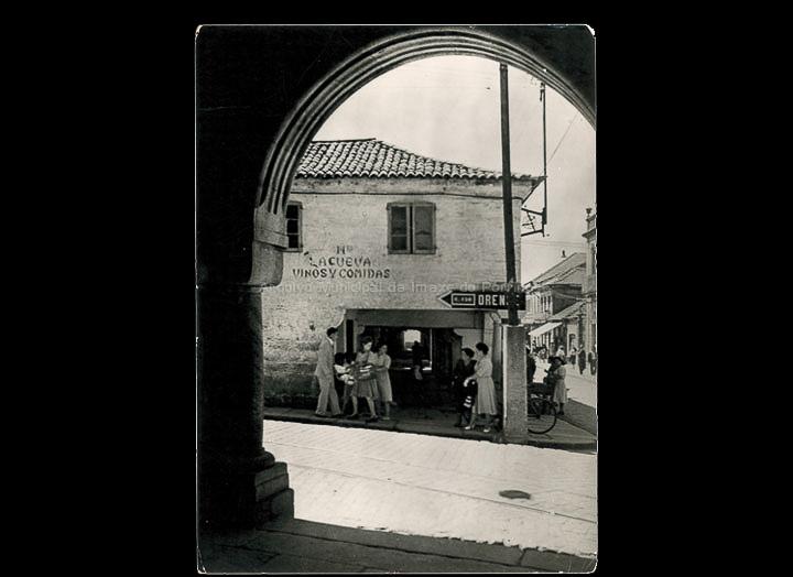 Bar La Cueva e soportais da rúa Ramón González. Tarxeta postal. / Multifoto-Conegliano (Italia) [1950-1960 (?)] / PROCEDENCIA: Recollida O Porriño. Album familiar de Pilar Losada Torres