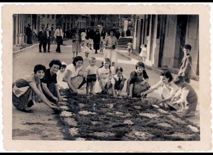Mozas e nenos de San Benito facendo unha das tradicionais alfombras de Corpus. / Foto Magno [Ca. 1960] / PROCEDENCIA: Recollida O Porriño. Album familiar de Carmen Domínguez Estévez