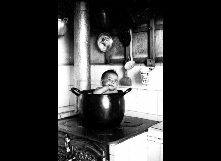 Nena bañándose nunha pota na cociña de ferro. / Foto Magno [1950 – 1970 (?)] / PROCEDENCIA: Arquivo Magno