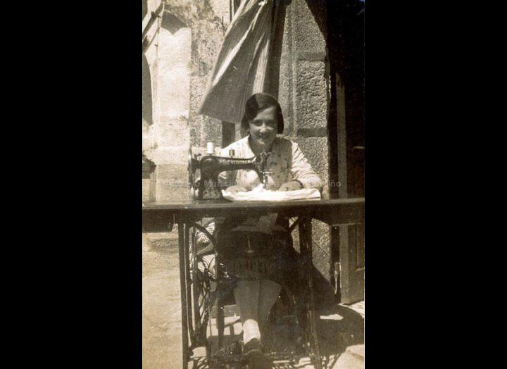 Josefina Casales Arias cosendo á máquina na porta da casa. / Autor descoñecido [1933 - 1943] / PROCEDENCIA: Recollida O Porriño. Album familiar de Josefa Sío Casales